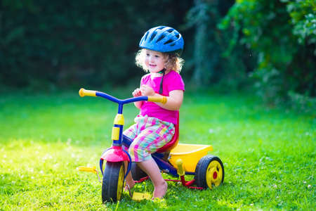 Children riding a bike. Kids enjoying a bicycle ride. Little preschooler girl having fun outdoors. Active toddlers play in the garden. Summer fun in a park. Child wearing safety helmet. photo