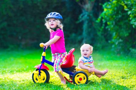 preescolar: Niños que montan en bicicleta. Los niños disfrutan de un paseo en bicicleta. Niña preescolar y bebé, hermano y hermana, divertirse al aire libre. Niños activos juegan en el jardín.