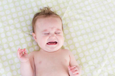 Little crying newborn baby on a green blanket 스톡 콘텐츠
