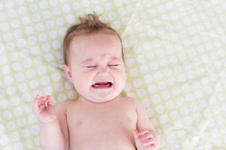 bebes niñas: Poco llorando bebé recién nacido en una manta verde Foto de archivo