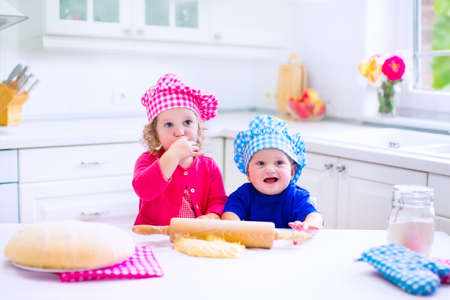 kitchen device: Kids baking. Two children cooking. Little girl and baby boy cook and bake in a white kitchen with modern oven. Brother and sister in chef hats making a pie for dinner.