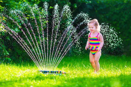 Child playing with garden sprinkler. Kid in bathing suit running and jumping. Kids gardening. Summer outdoor water fun. Children play with gardening hose watering flowers. Stock Photo