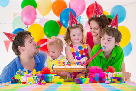 Happy family celebrating kids birthday. Parents and three children celebrate together. Child party with baloon decoration, cake with candles and present boxes. Celebration for baby boy, toddler girl and school kid. Archivio Fotografico