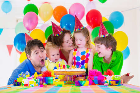 Happy family celebrating kids birthday. Parents and three children celebrate together. Child party with baloon decoration, cake with candles and present boxes. Celebration for baby boy, toddler girl and school kid. Standard-Bild