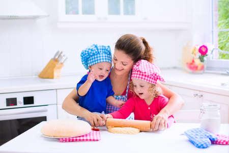 Kinderen en moeder bakken. Twee kinderen en ouders koken. Meisje en jongetje koken en bakken in een witte keuken met moderne oven. Broer en zus in chef hoeden maken van een taart voor het diner.