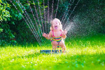 famiglia in giardino: Bambino che gioca con giardino sprinkler. Bambino in vestito di bagno correre e saltare. Bambini giardinaggio. Divertimento dell'acqua di estate all'aperto. I bambini giocano con i fiori irrigazione tubo giardinaggio. Archivio Fotografico
