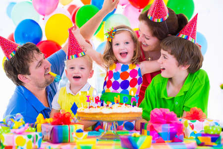 Happy family celebrating kids birthday. Parents and three children celebrate together. Child party with baloon decoration, cake with candles and present boxes. Celebration for baby boy, toddler girl and school kid. Stock Photo