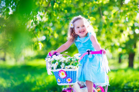 kids activities: Happy child riding a bike. Cute kid biking outdoors. Little girl in a blue dress on a pink bicycle with daisy flowers in a basket. Healthy preschool children summer activity. Kids playing outside. Stock Photo