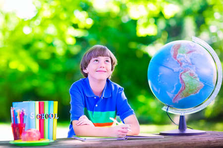 school yard: Child in school yard. Kids study. Happy laughing teenager student boy in the school garden reading books and having apple for healthy snack, back to school concept Stock Photo