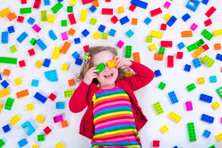 building bricks: Child playing with colorful toys. Little girl with educational toy blocks. Children play at day care or preschool. Mess in kids room. View from above. Stock Photo