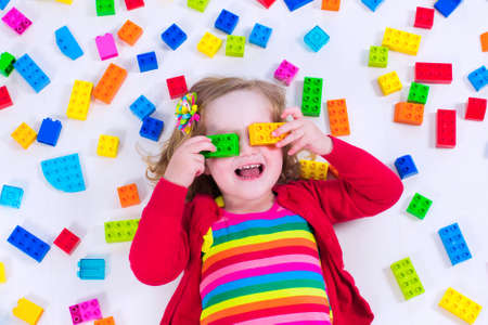 play: Child playing with colorful toys. Little girl with educational toy blocks. Children play at day care or preschool. Mess in kids room. View from above. Stock Photo