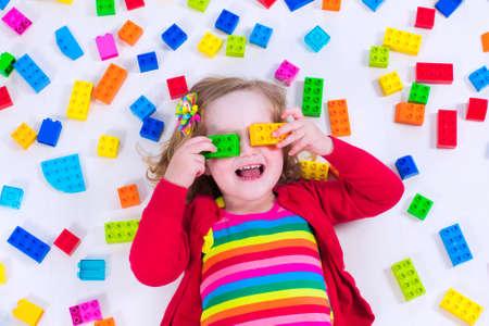 preescolar: Ni�o jugando con juguetes de colores. Ni�a con bloques de juguete educativos. Los ni�os juegan en la guarder�a o al preescolar. L�o en el cuarto de los ni�os. Ver desde arriba.