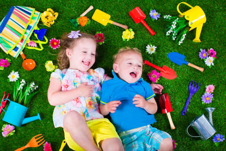 CHILD CARE: Kids gardening. Children with garden tools. Child with watering can and shovel. Little kid watering flowers. Girl and baby boy relaxing on green backyard lawn in summer. Stock Photo