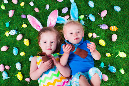 chocolate eggs: Children on Easter egg hunt. Kids eat chocolate rabbit. Boy and girl relaxing on a green lawn in the garden. Child enjoying sweets. Kid with bunny ears. Stock Photo