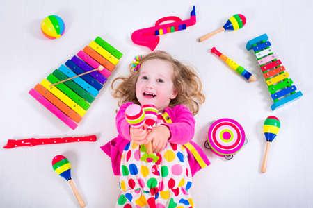 jugar: Niño con los instrumentos musicales. La educación musical para niños. Juguetes coloridos del arte de madera para niños. Niña que juega música. Cabrito con el xilófono, guitarra, flauta. Foto de archivo