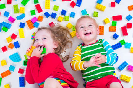 Niño jugando con juguetes de colores. Niña y niño con bloques de juguete educativos. Los niños juegan en la guardería o al preescolar. Lío en el cuarto de los niños. Ver desde arriba. Foto de archivo