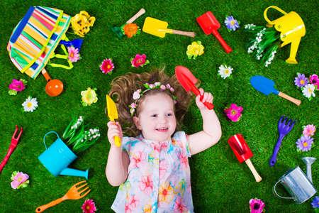 子供の園芸します。子供の庭ツール。じょうろとシャベルの子。小さな子供は、花に水をまきます。夏には緑の裏庭の芝生の上の女の子。