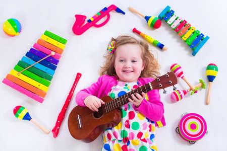 preescolar: Niño con los instrumentos musicales. La educación musical para niños. Juguetes coloridos del arte de madera para niños. Niña que juega música. Cabrito con el xilófono, guitarra, flauta. Foto de archivo