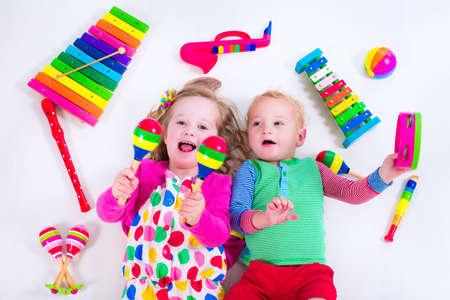 Kind met muziek instrumenten. Musical onderwijs voor kinderen. Kleurrijke houten art speelgoed voor kinderen. Meisje en jongen te spelen muziek. Kid met xylofoon, gitaar, fluit. Stockfoto