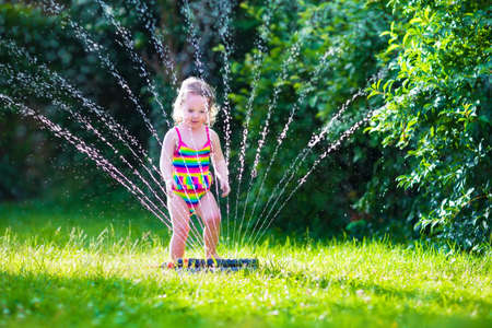 hosepipe: Child playing with garden sprinkler. Kid in bathing suit running and jumping. Kids gardening. Summer outdoor water fun. Children play with gardening hose watering flowers. Stock Photo