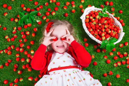 Child eating strawberry. Little girl playing peek a boo holding fresh ripe strawberries. Kids eating fruit relaxing on a lawn. Children summer fun on a farm picking berry. Stock Photo