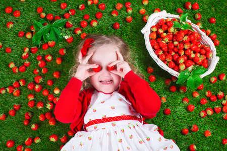 frutas divertidas: Niño que come la fresa. Niña jugando Peek a boo celebración de fresas frescas y maduras. Niños que comen fruta se relaja en un césped. Los niños la diversión del verano en una recolección de bayas granja. Foto de archivo
