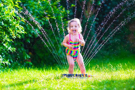 Child playing with garden sprinkler. Kid in bathing suit running and jumping. Kids gardening. Summer outdoor water fun. Children play with gardening hose watering flowers. Archivio Fotografico