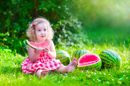 fruit in water: Child eating watermelon in the garden. Kids eat fruit outdoors. Healthy snack for children. Little girl playing in the garden holding a slice of water melon. Kid gardening. Stock Photo
