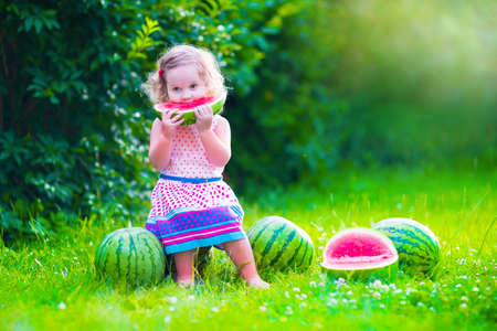 eating in: Child eating watermelon in the garden. Kids eat fruit outdoors. Healthy snack for children. Little girl playing in the garden holding a slice of water melon. Kid gardening. Stock Photo