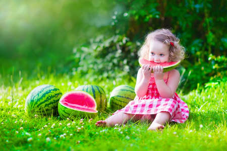 Child eating watermelon in the garden. Kids eat fruit outdoors. Healthy snack for children. Little girl playing in the garden holding a slice of water melon. Kid gardening. Zdjęcie Seryjne