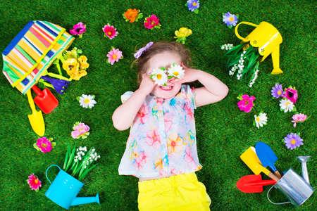 jardineros: Niños jardinería. Los niños con las herramientas de jardín. Niño con regadera y pala. Niño regando flores. Muchacha que se relaja en el césped del patio trasero verde en verano.