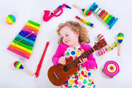 messy kids: Child with music instruments. Musical education for kids. Colorful wooden art toys for kids. Little girl playing music. Kid with xylophone, guitar, flute.