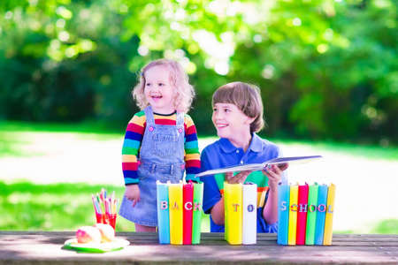 school yard: Children in school yard. Kids study. Happy laughing teenager student boy and preschool girl in the school garden reading books and having apple for healthy snack, back to school concept
