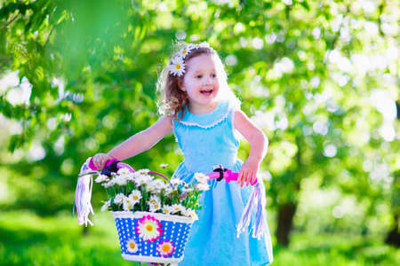 Happy child riding a bike. Cute kid biking outdoors. Little girl in a blue dress on a pink bicycle with daisy flowers in a basket. Healthy preschool children summer activity. Kids playing outside. photo