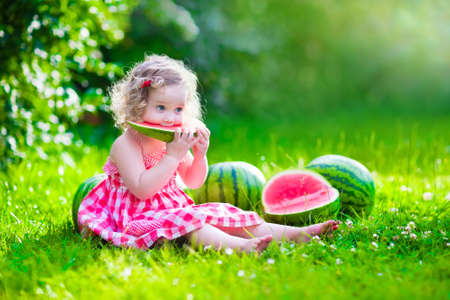 Child eating watermelon in the garden. Kids eat fruit outdoors. Healthy snack for children. Little girl playing in the garden holding a slice of water melon. Kid gardening. 스톡 콘텐츠