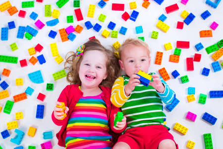 Child playing with colorful toys. Little gir and baby boyl with educational toy blocks. Children play at day care or preschool. Mess in kids room. View from above.