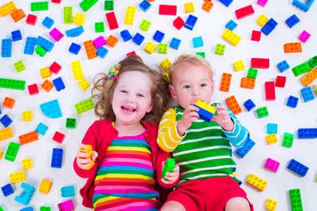 Niño que juega con los juguetes coloridos. Poco gir y boyl bebé con bloques de juguete educativos. Los niños juegan en la guardería o al preescolar. Lío en el cuarto de los niños. Ver desde arriba. Foto de archivo - 40333369
