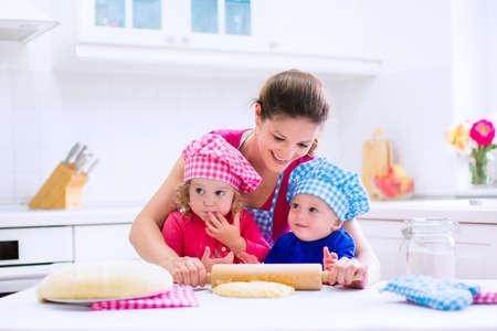 brothers playing: Los ni�os y la madre de hornear. Dos ni�os y cocinar los padres. Ni�a y ni�o cocinar y hornear en una cocina blanca con horno moderno. Hermano y hermana en sombreros del cocinero haciendo un pastel para la cena.