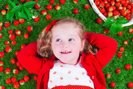 strawberry baskets: Child eating strawberry. Little girl playing peek a boo holding fresh ripe strawberries. Kids eating fruit relaxing on a lawn. Children summer fun on a farm picking berry. Stock Photo