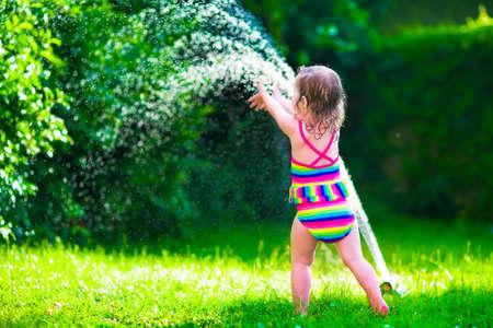 Niño que juega con la regadera de jardín. Kid en bañador correr y saltar. Niños jardinería. Diversión en el agua al aire libre de verano. Los niños juegan con flores manguera de jardinería riego.