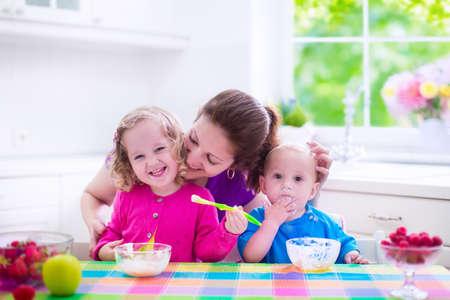 frutas divertidas: Familia que desayuna en una cocina blanca soleado. Madre joven que introduce dos hijos, comer frutas y productos l�cteos. Nutrici�n saludable para los ni�os - yogur, fresa y manzana. Padres con kid ni�o y beb� cocinar comida de la ma�ana. Foto de archivo