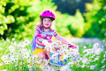Happy child riding a bike. Cute kid in safety helmet biking outdoors. Little toddler girl on a pink bicycle with daisy flowers in a basket. Healthy preschool children summer activity. Kids playing outside. photo