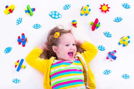 kinder: Niño jugando con aviones de madera. Preescolar chico volando alrededor del mundo. Niños viajando y jugando. Los niños en la guardería o jardín de infantes. Ver desde arriba. Foto de archivo