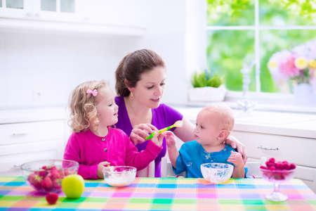 niños desayunando: Familia que desayuna en una cocina blanca soleado. Madre joven que introduce dos hijos, comer frutas y productos lácteos. Nutrición saludable para los niños - yogur, fresa y manzana. Padres con kid niño y bebé cocinar comida de la mañana. Foto de archivo