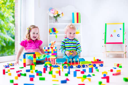messy kids: Kids play at day care. Two toddler children build tower of colorful wooden blocks. Child playing with toy train. Educational toys for preschool and kindergarten.