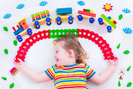 plaything: Child playing with wooden train. Toy railroad for kids. Toddler kid at day care. Educational toys for preschool and kindergarten child. Little girl at daycare.