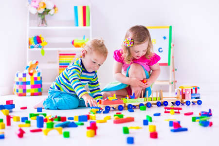 children playing with toys: Kids play at day care. Two toddler children build tower of colorful wooden blocks. Child playing with toy train. Educational toys for preschool and kindergarten.
