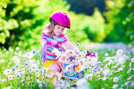 daisy pink: Happy child riding a bike. Cute kid in safety helmet biking outdoors. Little girl on a pink bicycle with daisy flowers in a basket. Healthy preschool children summer activity. Kids playing outside.