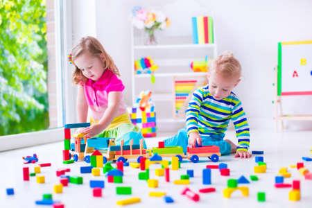 Kinder spielen am Tagespflege. Zwei Kleinkinder bauen Turm aus bunten Holzklötzen. Kind spielt mit Spielzeugeisenbahn. Pädagogische Spielwaren für Kinder im Vorschul und Kindergarten.