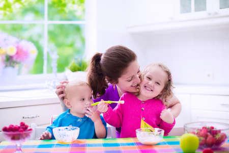 ni�os desayuno: Familia que desayuna en una cocina blanca soleado. Madre joven que introduce dos hijos, comer frutas y productos l�cteos. Nutrici�n saludable para los ni�os - yogur, fresa y manzana. Padres con kid ni�o y beb� cocinar comida de la ma�ana. Foto de archivo